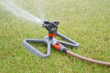 Lawn sprinkler spraying water over green grass poster