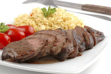 Sliced teryaki steak with rice pilaf and tomatoes.