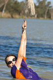 a teenage girl wearing goggles is hanging from a rope  poster