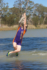 a teenage girl is swinging on a rope over a river in summer