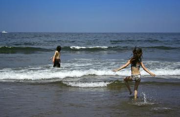 Children playing running to the ocean