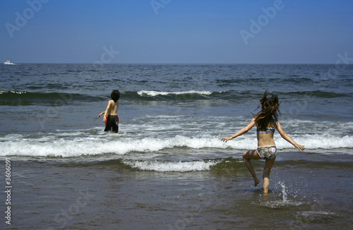 Children playing running to the ocean