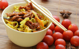 Chinese noodles and fried beef within bowl close-up poster