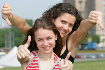 Two teen girls show thumbs up signs