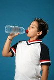 Thirsty boy drinking fresh water wearing sport clothes. poster