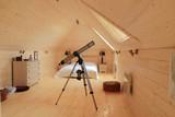 Wooden bedroom with telescope poster