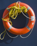 Orange life preserver ring with a rope poster