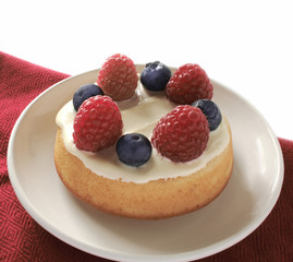small cake dessert  with raspberries and blueberries