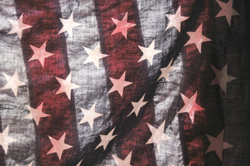 backlit old American flag showing stars over stripes