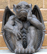 Scary looking Gargoyle sitting inside his wings