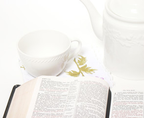 Open Bible, tea cup and tea pot