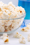 Closeup of glass bowl of popcorn and bottle of sparkling water poster
