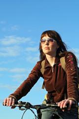 Glamour biker girl rushing along trees to sun