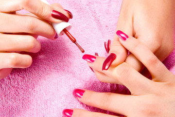 Young woman with beautiful long nails make the manicure