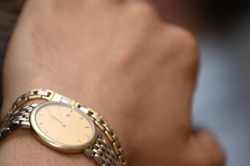gold watch on the man's hand