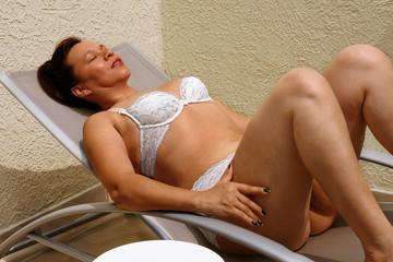 Mujer tomando el sol junto a piscina