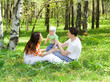 Family at nature. Three persons. Grass. Green forest.