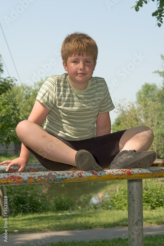 boy sits on gymnastic bars