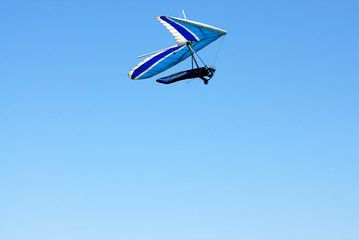 hang-glider with the blue wings in the Alps sky