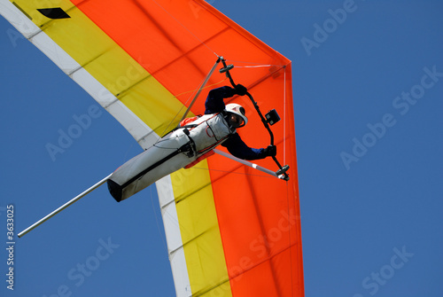 Yellow-red hang-glider under men control in the sky - 3633025