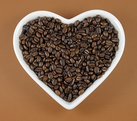 roasted coffee beans in a white heart shaped dish