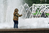 The little girl, a fountain and gushing foam. poster