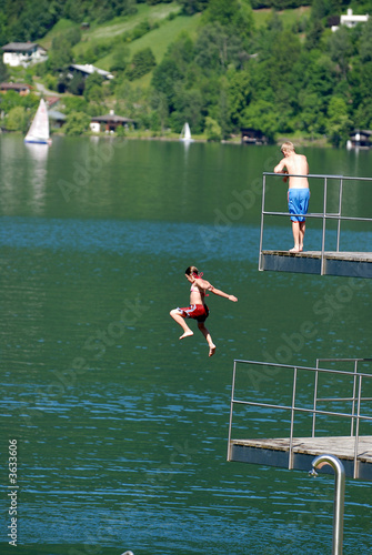 Kids are jumping from the tower to the lake