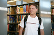 A young student in the library with a backpack