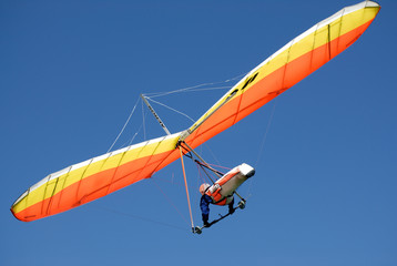 Orange-yellow hang-glider in the steep turn