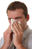 A young man with allergies sneezing into a tissue poster
