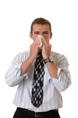 A businessman holding a tissure to his nose while he sneezes