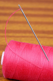 Detail of a needle with thread in a coil poster