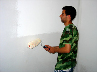 The young builder is painting the wall in the room