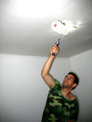The young builder is painting the ceiling in the room