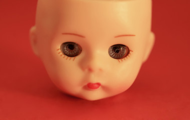 A close up of a doll's head on a red background