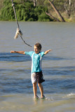 young boy is swinging on a rope looks like walking on water poster