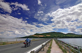 Biker on the road under amazing sky with clouds - summer poster