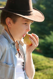 Diet Nutrition - A boy eating a fresh apple in the countryside. poster