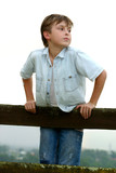 Child standing on a timber fence on an overcast afternoon. poster