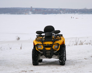 The yellow cross-country vehicle in the winter on a snow floor.