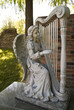 A statue of an angel playing a a large floor harp.