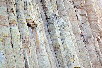 mountain climber ascending devil's tower in wyoming