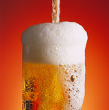 Pouring a glass of beer with a lot of foam