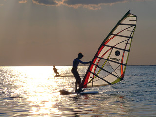A women is learning windsurfing at the sunset