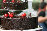 Dark chocolate mousse cake with cream and a strawberry poster