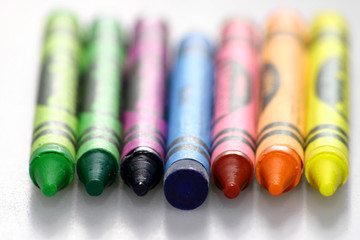 Crayons lined up on white background one reversed