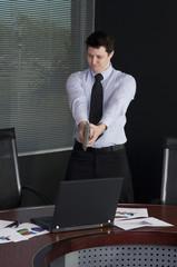 Businessman shooting his laptop computer with a handgun