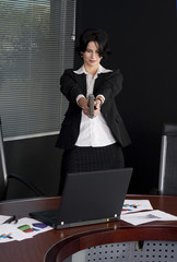 Businesswoman shooting her laptop with a handgun