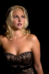 Beautiful blond woman in corset on black background