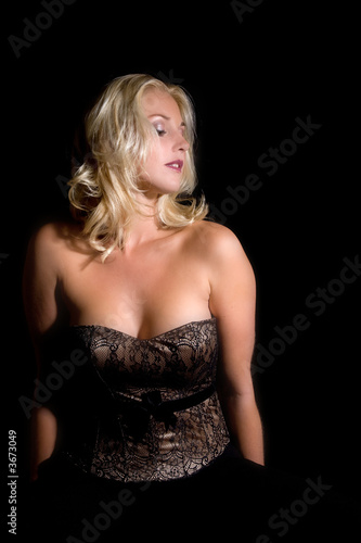 Beautiful blond women with a corset on black background